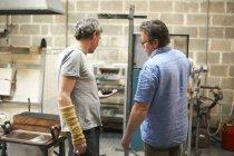 Мужчина, стеклодув в мастерской, смотрит на объект — стоковое фото