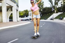 Молода жінка, скейтбординг вздовж дороги — стокове фото
