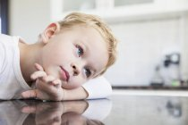 Portrait of preschooler boy leaning on kitchen bench — Stock Photo