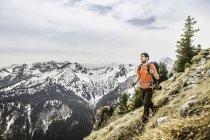 Joven excursionista masculino en el pico de la montaña Klammspitze, Oberammergau, Baviera, Alemania - foto de stock