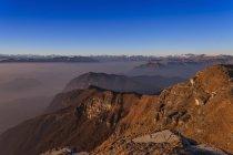 Paysage brumeux surélevée avec neige lointain les montagnes enneigées — Photo de stock