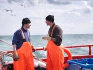 Fishermen on fishing boat talking — Stock Photo