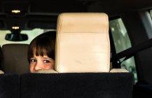 Ritratto di ragazzo felice che osserva sopra la sua spalla dal sedile posteriore auto — Foto stock