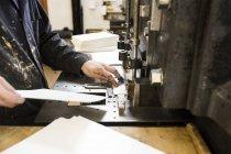 Мужской принтер готовит бумагу для печатного оборудования в типографии — стоковое фото