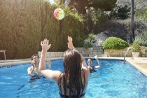 Teenage girl throwing ball to mother and brother in swimming pool — Stock Photo