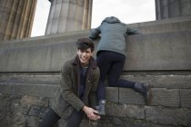 Молодой человек помогает своей девушке подняться на Национальный Монумент на Калтон Хилл в Эдинбурге, Шотландия — стоковое фото