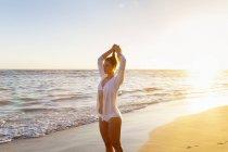 Молода жінка, роблячи хвіст волосся на пляжі на захід сонця, Домініканська Республіка, Карибського моря — стокове фото
