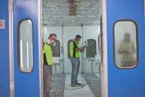 Men working in spray painting workshop — Stock Photo