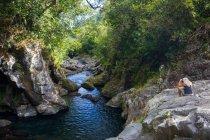 Женщина-туристка на скалах фотографирует реку тропических лесов, остров Реюньон — стоковое фото