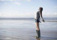 Giovane donna in piedi sulla spiaggia guardando in alto, Brean Sands, Somerset, Inghilterra — Foto stock