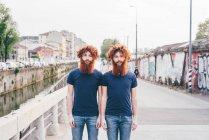 Портрет молоді чоловіки hipster близнюки з рудим волоссям і Борідки стоячи на мосту — стокове фото