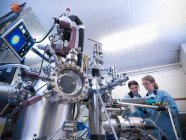 Scientists working together in front of materials science chamber — Stock Photo