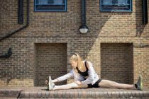 Runner stretching on walkway, Wapping, London — Stock Photo
