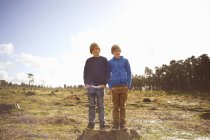 Portrait of twin brothers in forest clearing — Stock Photo