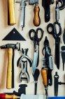 Tesouras e ferramentas penduradas na parede no estúdio de artes — Fotografia de Stock