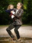 Батько тримає дочку в той час як хлюпалися в калюжі — стокове фото