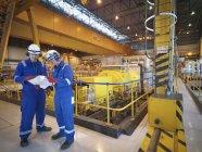 Робітники, які читають ноти в турбінному залі електростанції — стокове фото