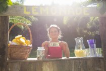Portrait of proud girl on lemonade stand holding up one dollar bill — Stock Photo