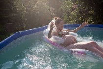 Pregnant woman floating in pool — Stock Photo