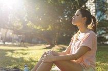 Jeune femme assise dans le parc avec les yeux fermés, Manille, Philippines — Photo de stock