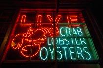 Shellfish shop neon sign in shop window — Stock Photo