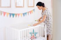 Pregnant mid adult woman measuring crib in childs nursery — Stock Photo