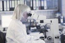 Cientista usando microscópio em laboratório — Fotografia de Stock