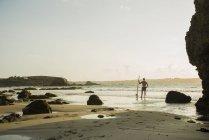 Reifer Mann steht am Rand des Wassers halten Surfbrett — Stockfoto