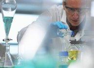 Биотехнология, ученый готовит химическую формулу во время эксперимента в лаборатории — стоковое фото