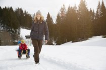 Woman pulling sons on toboggan in snow covered landscape, Elmau, Bavaria, Germany — Stock Photo