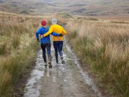 Rear view of male and female running on dirty path in mountain landscape — Stock Photo