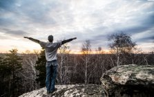 Young man with arms outstretched on top of rock formation at sunset — Stock Photo