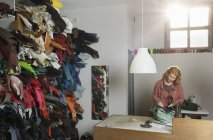 Mulher na bancada na oficina montagem de couro holdall — Fotografia de Stock