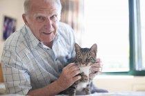 Портрет пожилого человека, ласкающего домашнюю кошку — стоковое фото