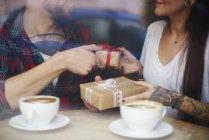 Blick durch die Fenster des Paares im Coffee-Shop, Austausch von Geschenken — Stockfoto