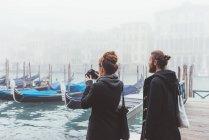 Пара фотографирующих гондолы на туманном канале, Венеция, Италия — стоковое фото