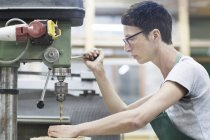 Woman in workshop using drilling machinery — Stock Photo