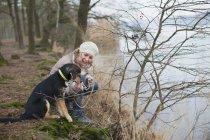 Взрослая женщина приседает со своей собакой на берегу реки — стоковое фото