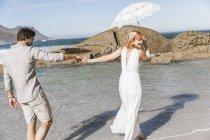 Paar hält sich an den Händen, geht mit Regenschirm über die Schulter und lächelt — Stockfoto