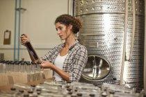 Frau schaut in Brennerei auf Flasche — Stockfoto