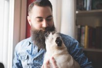 Young bearded man carrying dog in arms — Stock Photo