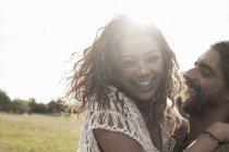Retrato de joven pareja abrazaba mirando a la cámara sonriendo - foto de stock