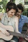 Молода пара серенади на акустичній гітарі в парку — стокове фото