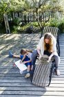Mother using tablet, daughter drawing on wooden decking — Stock Photo