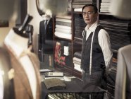 Tailor standing behind counter in tailors shop — Stock Photo