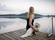 Frau mit coton de tulear Hund mit Blick von der Seebrücke, orivesi, Finnland — Stockfoto