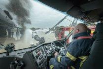 Пожарные в кабине пожарной машины на учебном полигоне аэропорта — стоковое фото
