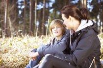 Donna matura che si prende una pausa con suo figlio in una foresta — Foto stock