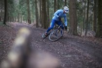Cyclist on tree lined dirt track wearing cycling helmet falling off bicycle — Stock Photo