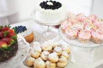 Selección de pasteles y postres en la mesa - foto de stock